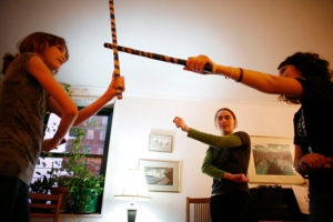 Jess Kjellberg (center) instructs Isabel Ringer (left) and her friend Elena Milin (right) in the art of Escrima or stick fighting./Kirsten Luce